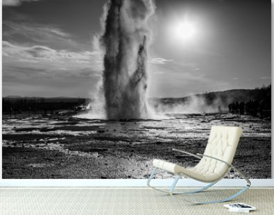 Eruption of Strokkur geyser in Iceland. Winter cold colors, sun lighting through the steam. Geothermal area in Iceland