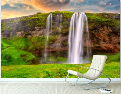 Seljalandsfoss waterfall in Iceland at sunset, amazing summer landscape, panoramic view with green flowering meadow and falling water from the cliff, travel background, popular tourist attraction