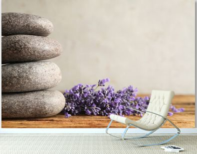 Lavender flowers and spa stones on wooden table, closeup. Space for text