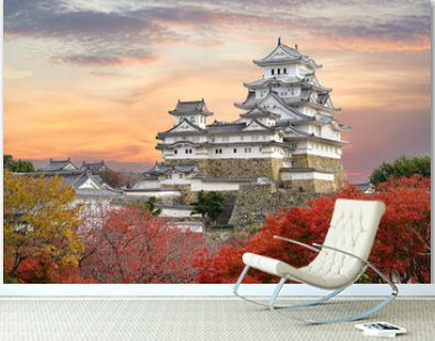 Himeji Castle and red maple leaves in evening sunlight and twilight sky in Himeji city, Hyogo prefecture of Japan.