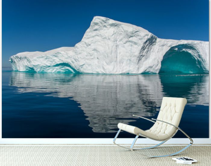 Reflection of iceberg. Big wall with arch and still water.