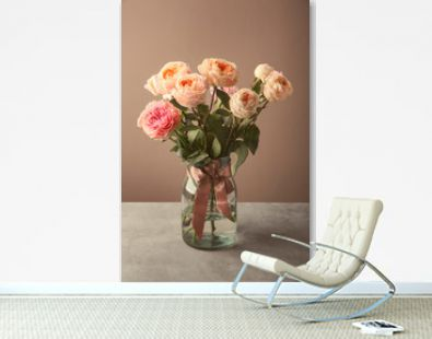 Vase with bouquet of beautiful roses on table against color background