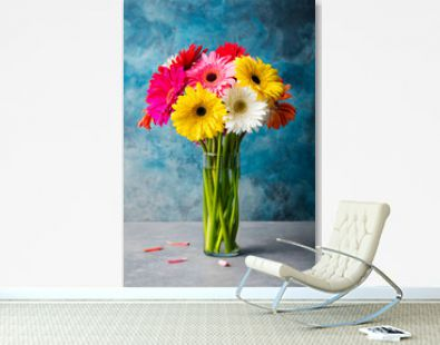 Colorful bunch of gerbera flowers in a glass vase.