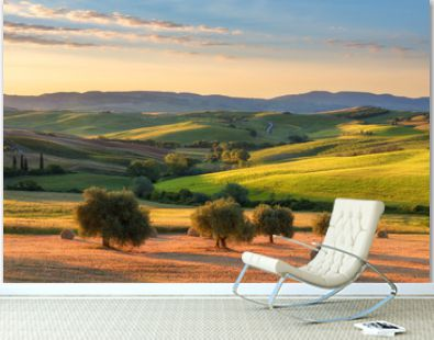 Magnificent spring landscape at sunrise.Beautiful view of typical tuscan farm house, green wave hills, cypresses trees, hay bales, olive trees, beautiful golden fields and meadows.Italy, Europe
