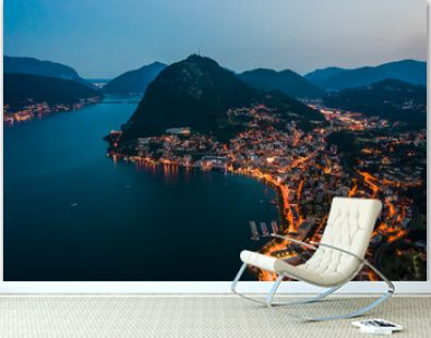 High angle aerial drone night shot of city street lights by lake monte salvatore in Lugano, Switzerland
