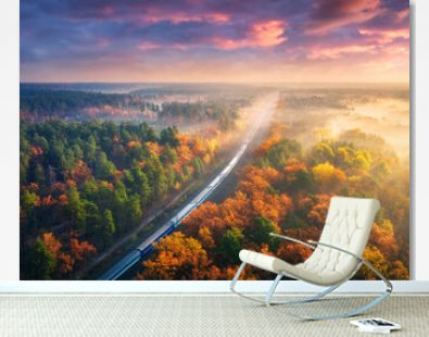 Aerial view of passenger train in beautiful forest in fog at sunset. Autumn landscape with railroad, foggy trees, trail and colorful sky with clouds. Top view of moving train in fall. Railway station