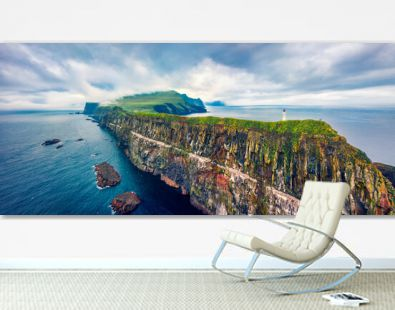 Panoramic view from flying drone of Mykines island with old lighthouse. Gloomy summer scene of Faroe Islands, Denmark, Europe. Stunning seascape of Atlantic ocean.
