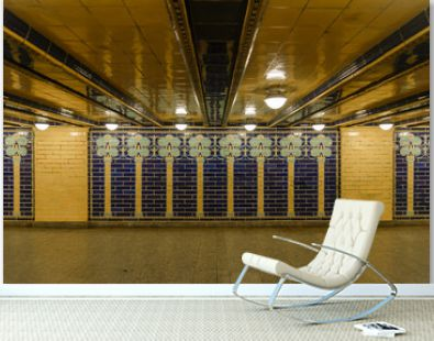 Interior view of the vintage yellow and blue tiles pattern on the wall along passage of underground metro station.