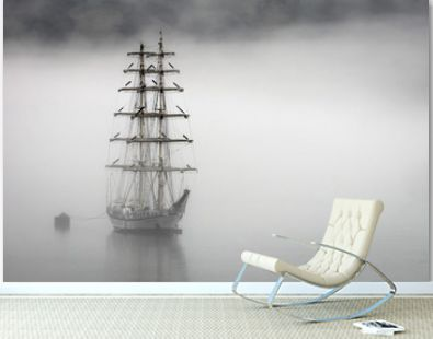 A sailboat in the Geiranger fjords in Norway during very foggy weather.