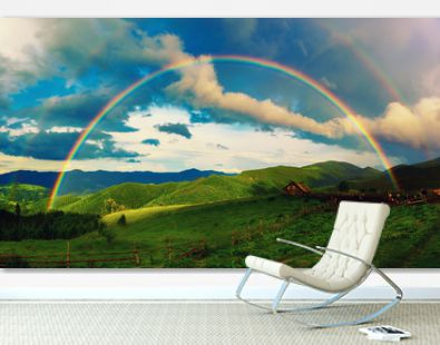 Beautiful mountain valley with green hills and huge rainbow in summer. Natural outdoor travel background. Carpatians, Ukraine