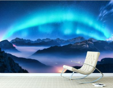 Aurora borealis above mountains in fog at night. Northern lights. Sky with stars with polar lights and high rocks. Beautiful landscape with aurora, city lights in low clouds, mountain ridge. Space
