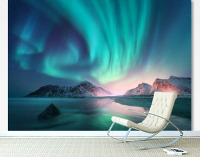 Aurora borealis over the sea and snowy mountains. Northern lights in Lofoten islands, Norway. Sky with polar lights and stars. Winter landscape with aurora, reflection, sandy beach at starry night