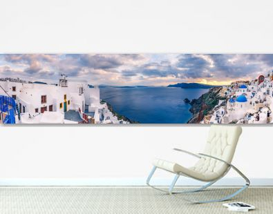 Panorama view on Oia, Santorini island in Greece, at sunset. Scenic travel background.