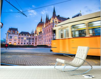 Old yellow tram speeds up along city streets at night. The historical center of the capital of Hungary