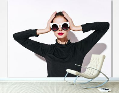 woman model in a black sweater and sunglasses holds her hands on her head