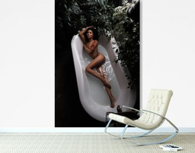 A sensual and tempting african american beautiful female model with slim gorgeous body is lying and posing in the bath full of water in the jungles. Relax, dark foliage is around the woman