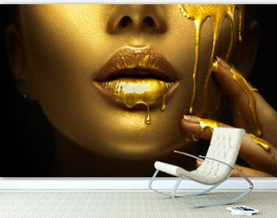 Golden paint smudges drips from the face lips and hand, golden liquid drops on beautiful model girl's mouth, creative abstract makeup. Beauty woman face