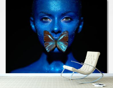 Fashion model woman in blue bright sparkles and neon lights posing in studio. Portrait of beautiful sexy woman with blue butterfly. Art design colorful glitter glowing make up