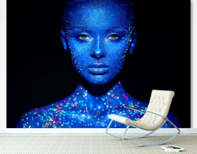 Fashion model woman in blue bright sparkles and neon lights posing in studio. Portrait of beautiful sexy woman. Art design colorful glitter glowing make up