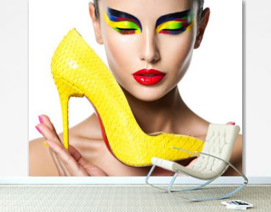 beautiful woman with vivid make-up of eyes holds the yellow high heel