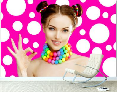 A bright girl model shows okay hand, fingers. Beautiful, stylish, young woman in a candy doll style with massive beads around her neck