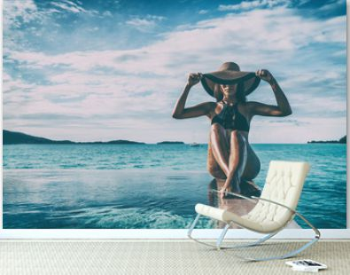 Elegant black swimsuit model woman high end fashion with sun hat on infinity poolside luxury resort vacation for wellness spa concept, hair removal laser legs and body.