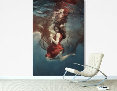 Girl in a red dress with a cloth swims underwater