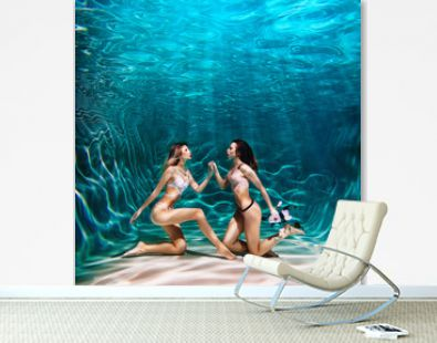 Two girls posing underwater in fashion underwear with flowers in hands in swimming pool together in the deep