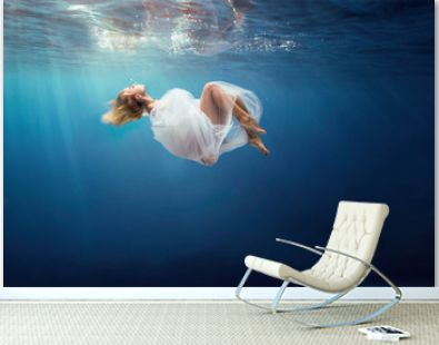 Blonde girl wrapped in fine white cloth, sank in blue deep water of ocean, against dark sea background.