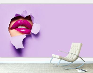 Beautiful plump bright lips of pink color peep into the slit of colored paper.