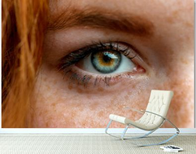 Close up of one eye of young red ginger freckled woman with perfect healthy freckled skin, looking at camera. Ophthalmology, Vision care