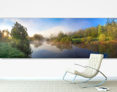 rural panorama with river, fog and forest at sunrise
