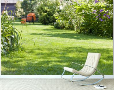 beautiful garden, full of green plants and colorful flowers with an armchair in the background