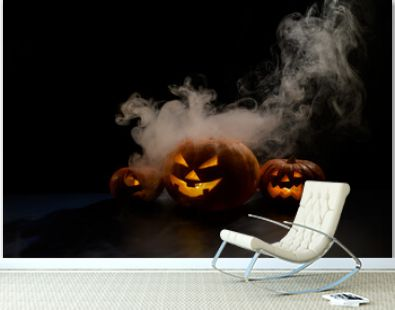 Three creepy halloween steaming pumpkins with a carved luminous smirk on a black background. A handmade jack-o-lantern head with a candle inside in the dark among the fog. Trick or treat. Postcard.