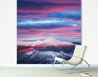 Fantastic orange winter landscape in snowy mountains glowing by sunlight. Dramatic wintry scene with snowy trees. Christmas holiday background