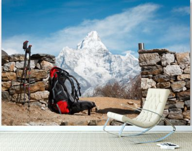 A backpack, hiking poles and a mug on the background of Mount Ama Dablam. The mountain is blurred. Everest trekking. Nepal.