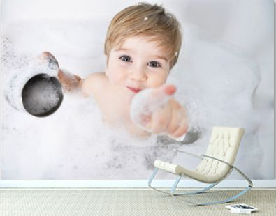 small child takes a bath with foam