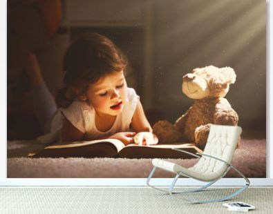 Little child girl is reading a book in evening in dark with a toy bear.