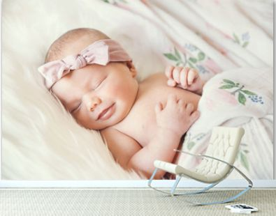 Sleeping smiling newborn baby in a wrap on white blanket.