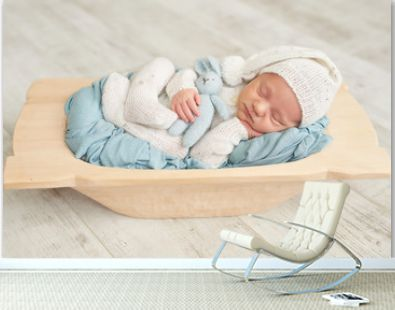 Cute newborn little boy sleeping in crib with toys. Baby goods packaging template. Closeup portrait of newborn baby with smile on face. Healthy and medical concept.