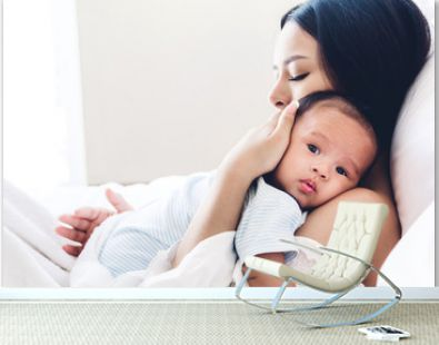 Mother holding baby in her arms and kiss in a white bedroom.Love of family concept