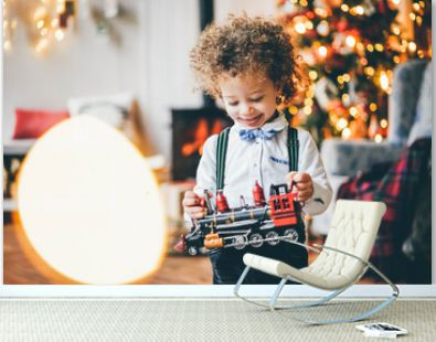 Mixed race little cute boy playing with toy train in the xmas morning.