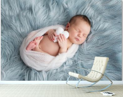 The sleeping Newborn gilr or boy lies on the blue fur. White heart in her or him hands.