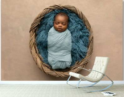 sleepy swaddled African-American newborn baby boy laying on a blue rug in a basket with copy space