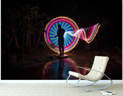 One person standing alone against beautiful Colourful circle light painting as the backdrop