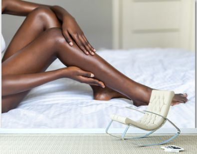 Close up of young dark skin woman with perfect body touching gently her hairless soft and silky legs after depilation in bed at home