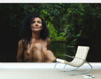 A young sexual naked woman with black curly hairs is sitting in the tropical creek surrounded by jungle. Image. Nude Portrait Photography.