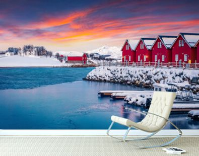 Typical red wooden houses on the shore of Offersoystraumen fjord. Fantastic winter sunset on Vestvagoy island. Colorful evening view of Lofoten Islands, Norway, Europe. Life over polar circle.