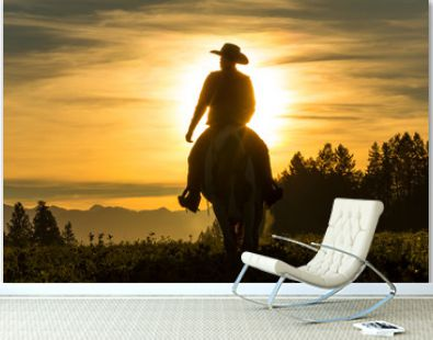 Cowboy riding across grassland with moutains behind, early moring, British Colombia, B.C., Canada