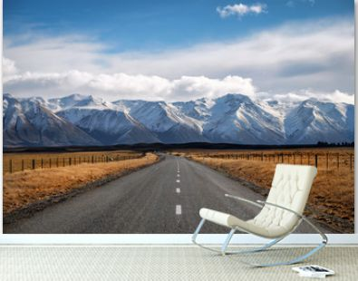 A long straight road path journey towards snow mountains in New Zealand.